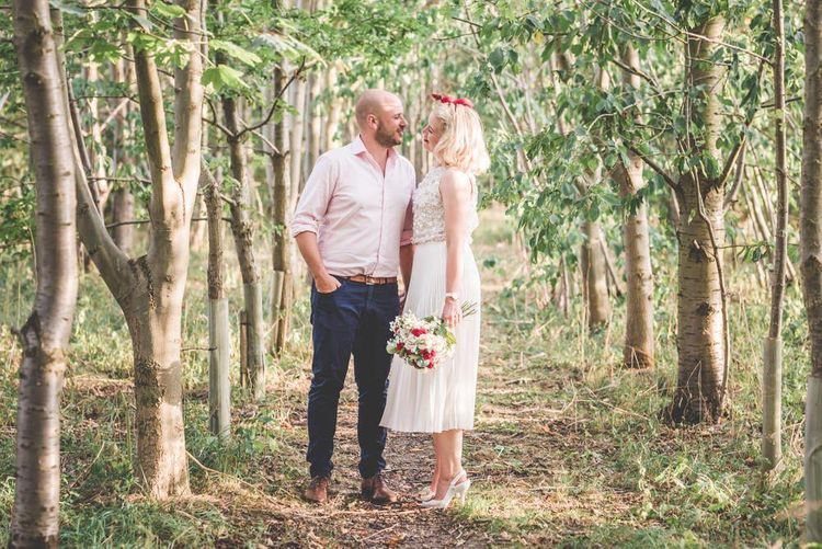 Bride and groom steal a moment in woodlands wearing pleated midi wedding skirt