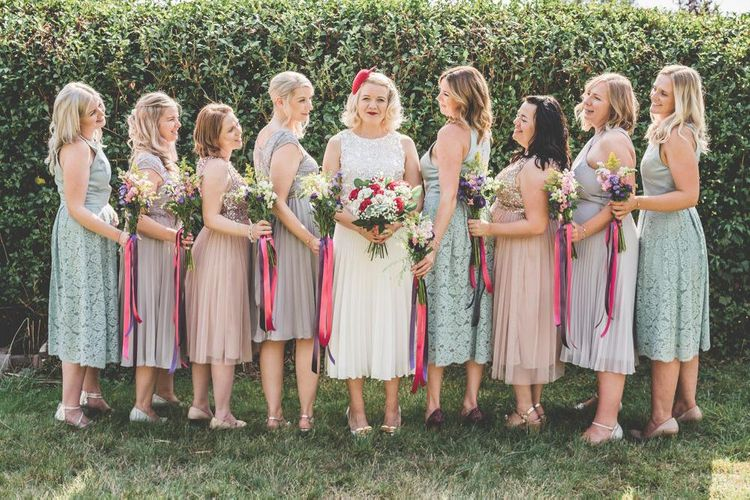 Bride wearing midi wedding skirt and bridesmaids with midi dresses in nude and duck egg