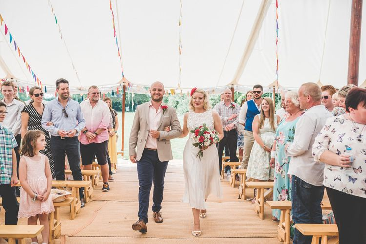 Bride and groom walking down the aisle together wearing midi wedding skirt with bunting decoration