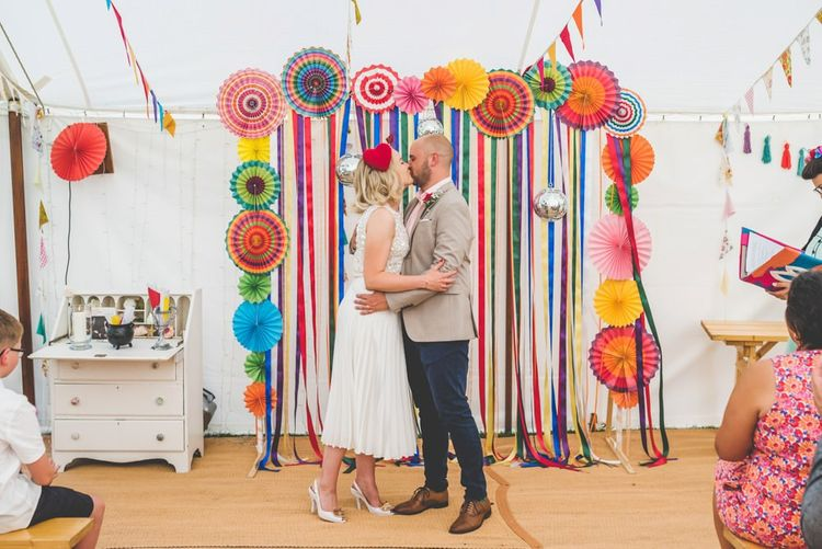 Bride and groom say 'I do' with bright ribbon decor and paper lantern decoration