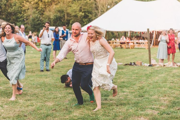 Three legged race at this fun village fete themed wedding party with midi wedding skirt