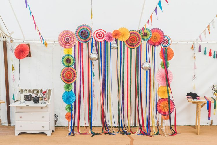 Bright ribbon and homemade bunting with colourful paper lantern decorations at fete themed celebration