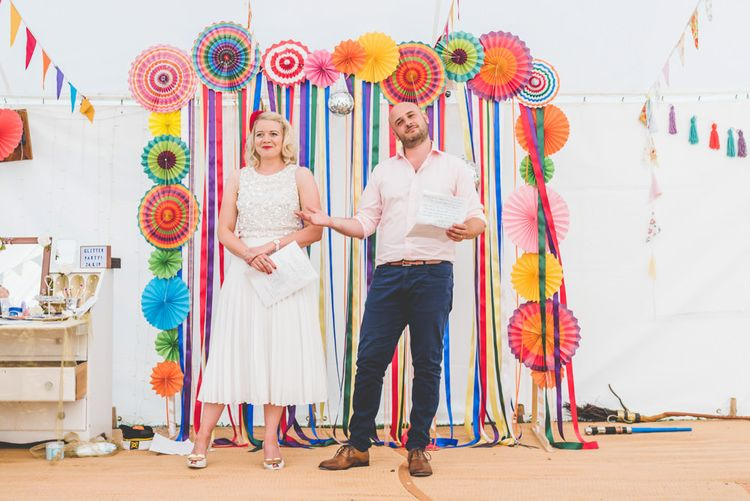 Bride and grooms first speech with midi wedding skirt and bright ribbon decor with colourful paper fans
