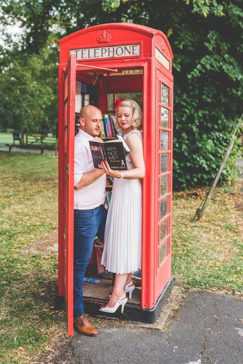 Bride and groom enjoy a moment together for a fun shoot inside telephone box