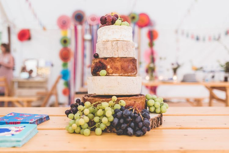 Cheese tower wedding cake with bright colourful ribbon and paper fan decorations
