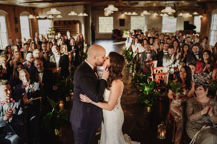 Bride in Martina Liana Lace Wedding Dress and Groom in Tom Ford Suit Kissing at the Altar
