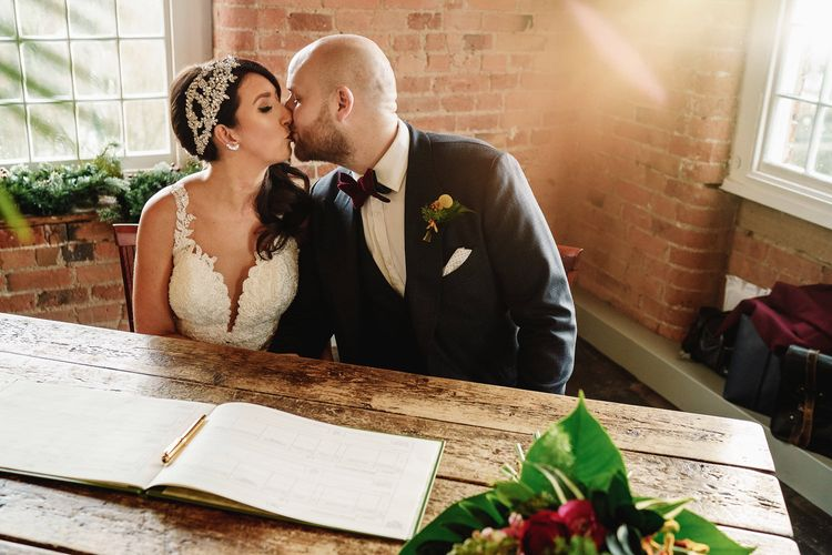 Bride in Martina Liana Lace Wedding Dress and Groom in Tom Ford Suit  Signing The Register