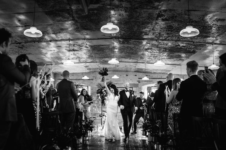 Bride in Martina Liana Lace Wedding Dress and Groom in Tom Ford Suit Walking Up The Aisle as Husband and Wife