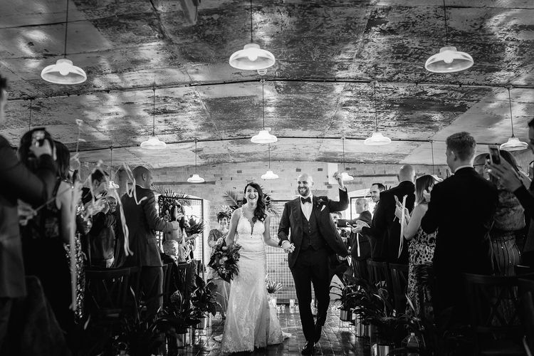 Bride in Martina Liana Lace Wedding Dress and Groom in Tom Ford Suit Walking Up The Aisle After Being Just Married