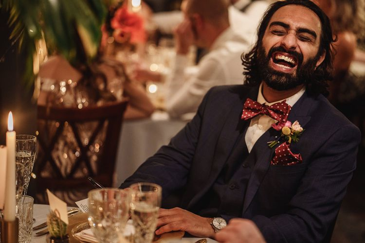 Groomsman in Navy Suit and Red Bow Tie Laughing During Wedding Reception Speeches