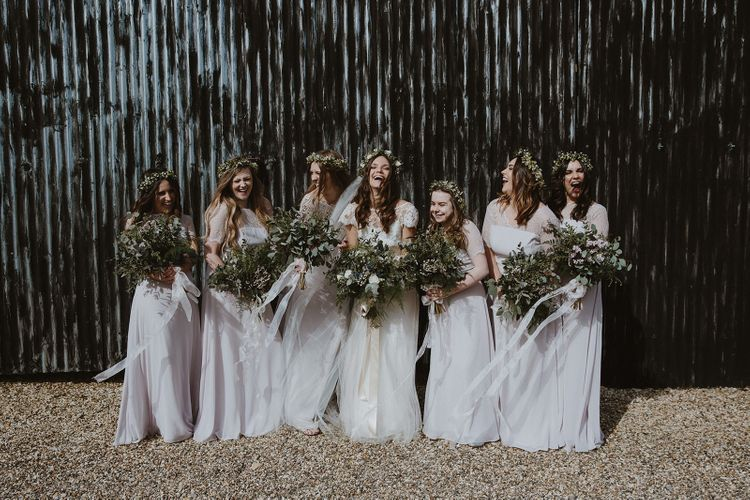 Bride and Her Bridesmaids in White Dress and Flower Crowns Laughing Together
