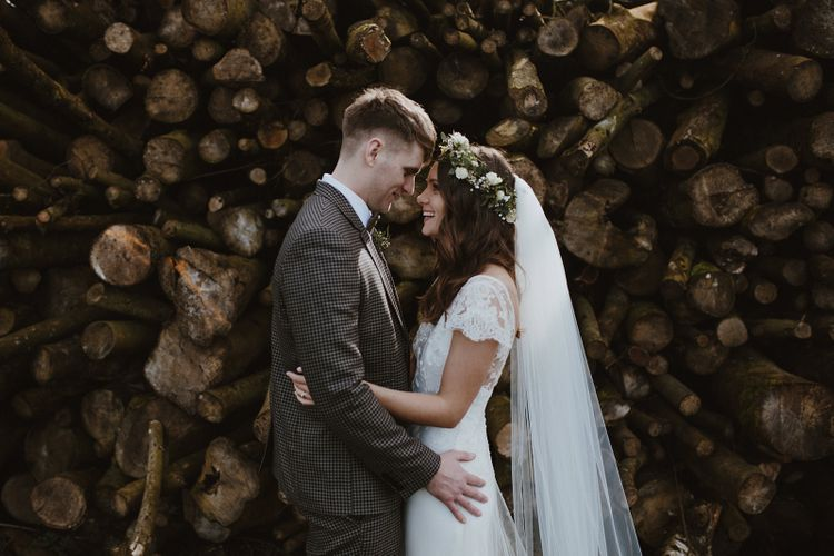 Bride in Iris Halfpenny London Gown and Groom in Brown Check Suit Embracing