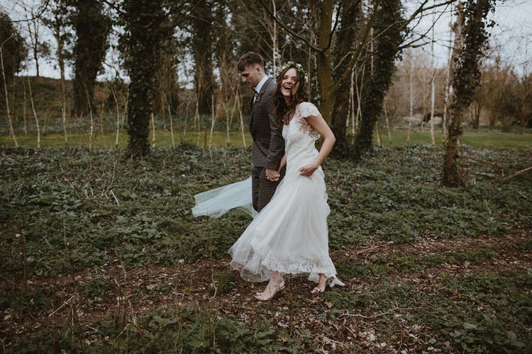 Bride and Groom Walking Through the Woods Laughing