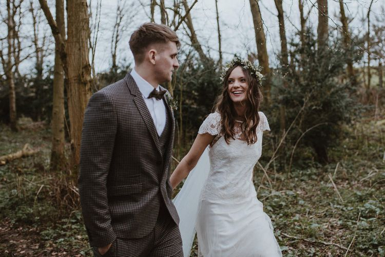 Bride in Flower Crown and Halfpenny London Wedding Dress and Groom in Brown Check Suit Holding Hands