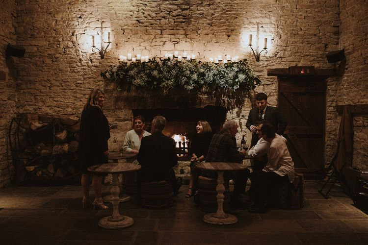 Wedding Guests Sitting Around the Rustic Fireplace with Over Mantel Wedding Flowers