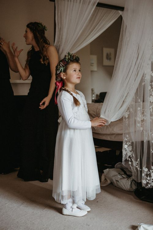 Flower girl in white dress with flower crown