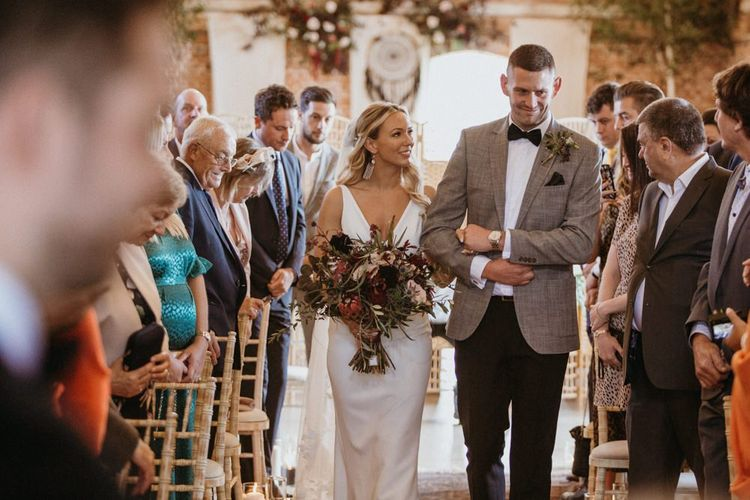 Bride walks down the aisle at rustic ceremony