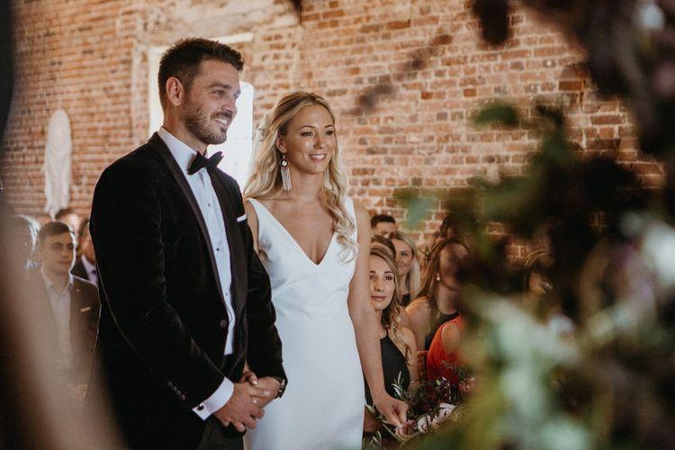 Bride and groom at altar at Norfolk wedding with  supermarket wedding cake