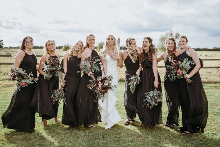 Black bridesmaid dresses alongside minimalist wedding dress