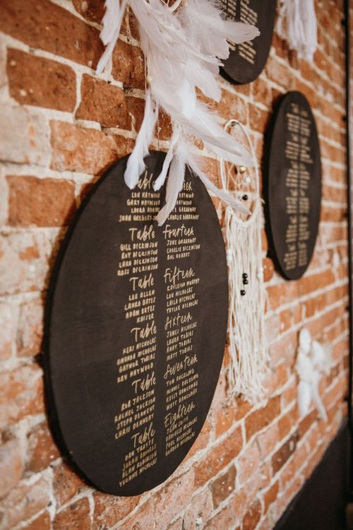 Chalkboard seating charts with dream catcher wedding decor