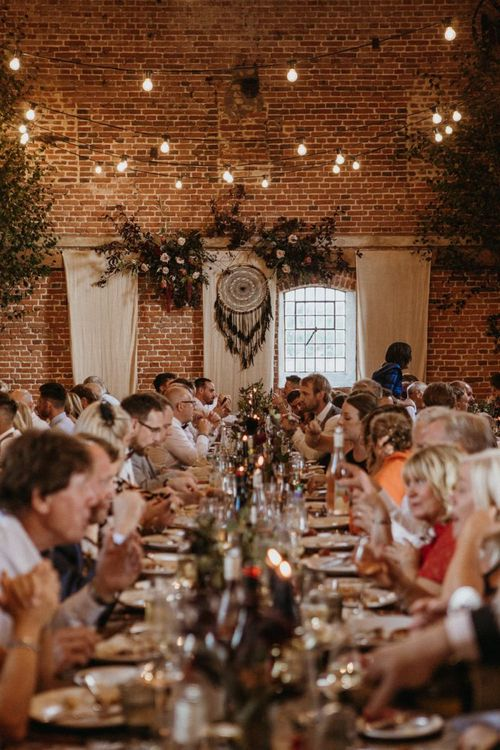 Wedding guests enjoy dinner and supermarket wedding cake beneath the festoon lighting