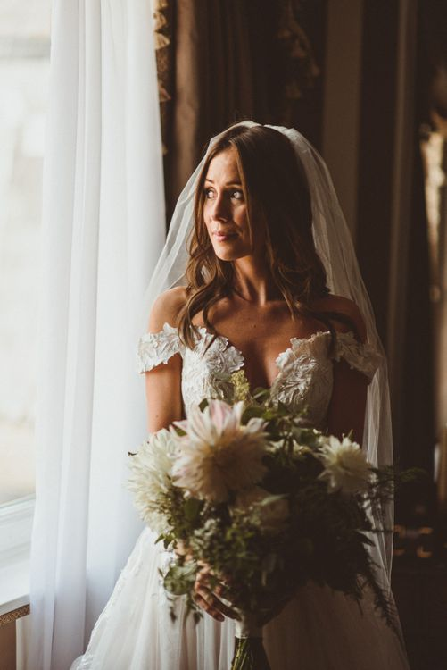 Bride wearing off the shoulder laced Martina Liana dress with veil and white foliage bouquet