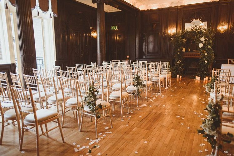 Reception styling with white foliage arch decor and pillar candles