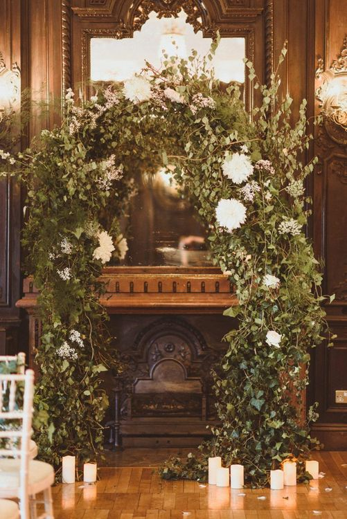White floral and foliage archway with pillar candles and scattered petals