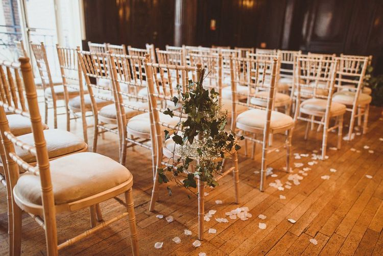 White floral chair back decor with scattered petals at London reception