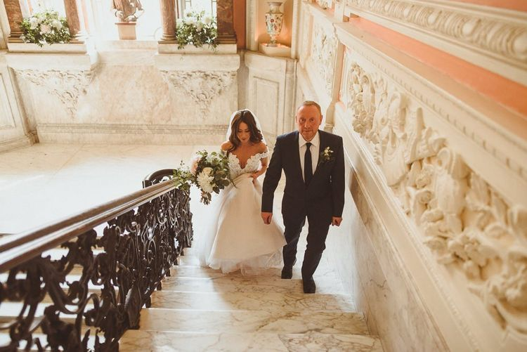 Bride wearing Martina Liana dress and her father walking up the stairs styled with white foliage decor