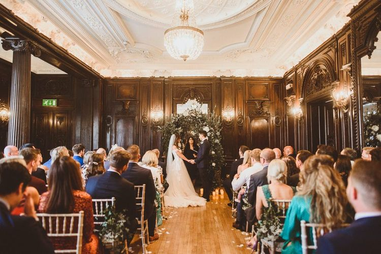 Bride and groom tie the knot at London ceremony with white foliage archway and floral chair back decor