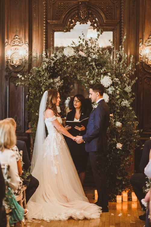 Bride and groom tie the knot at London ceremony with white foliage archway and pillar candles