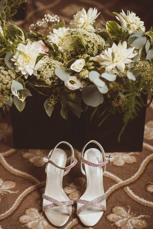 Silver embellished bridal shoes with white foliage bouquet