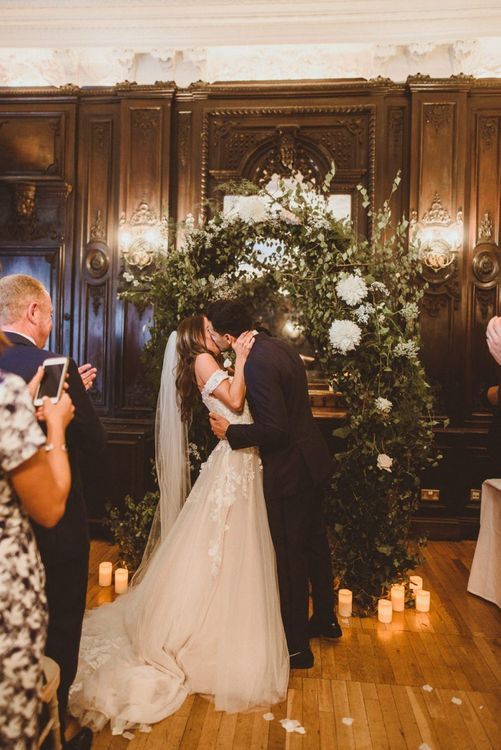 Bride and groom kiss with white foliage archway and candles scattered with petals