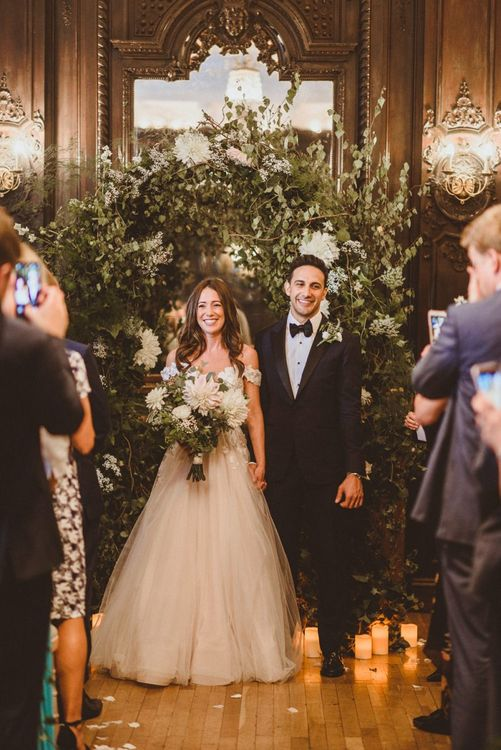 Husband and wife at London ceremony with white foliage decor