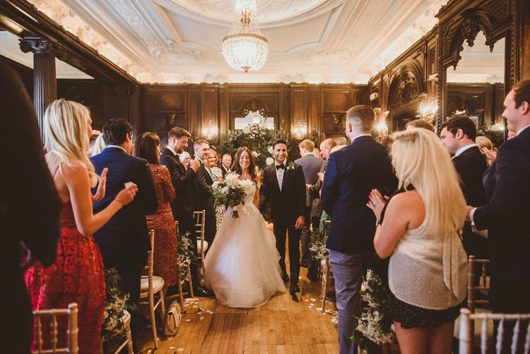 Husband and wife at London ceremony with white foliage styling and floral chair back decor