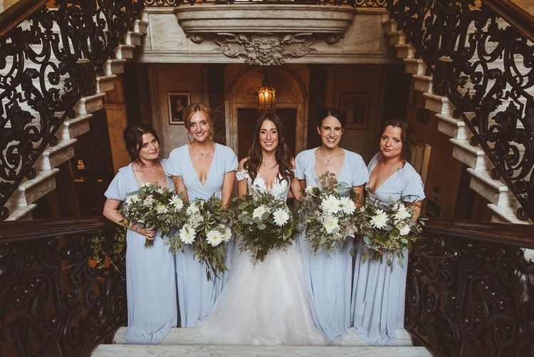 Bride wearing Martina Liana with her bridesmaids in pale blue dresses and white foliage bouquets