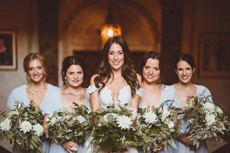 Bride wearing Martina Liana dress with her bridesmaids in pale blue dresses and white foliage bouquets