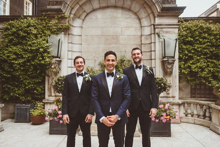 Groom and his groomsmen in black tie with white floral buttonholes