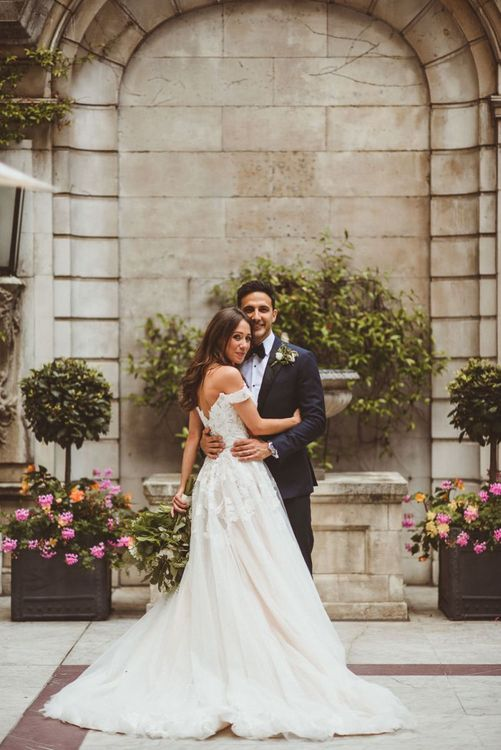 Bride wearing Martina Liana off the shoulder dress embraces with groom at London wedding