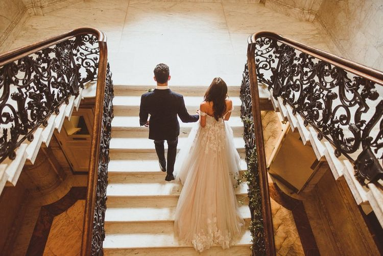 Bride and groom steal a moment on the stairway at Dartmouth House wedding in London