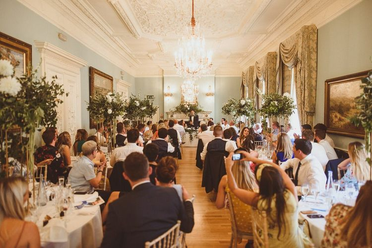 Guests celebrate the big day at beautiful London venue with tall floral centrepieces