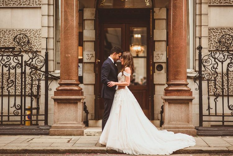 Bride and groom steal a moment wearing Martina Liana off the shoulder laced dress with tulle skirt