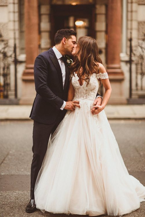 Bride wearing off the shoulder laced dress with tulle skirt