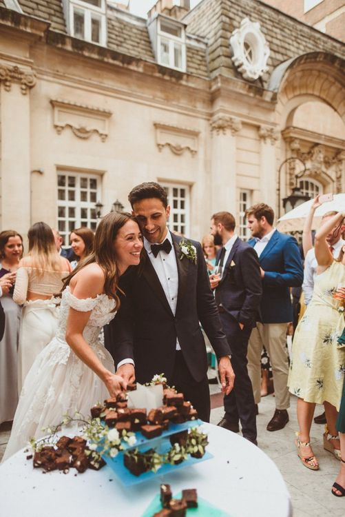 Bride and groom tuck into brownie tier wedding cake at outdoor drinks reception in London