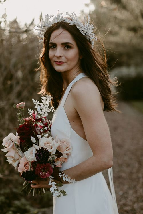 Bride in Halfpenny London Juniper Dress & Lilly Skirt and Luna Bea Headdress Holding a Deep Red and Blush Pink Winter Wedding Bouquet