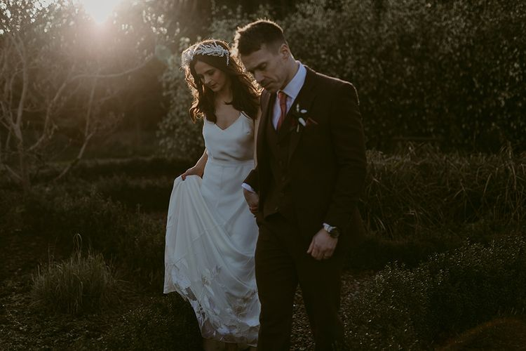 Bride in Halfpenny London Juniper Dress & Lilly Skirt and Luna Bea Headdress with Groom in Brown Wool Suit Holding Hands