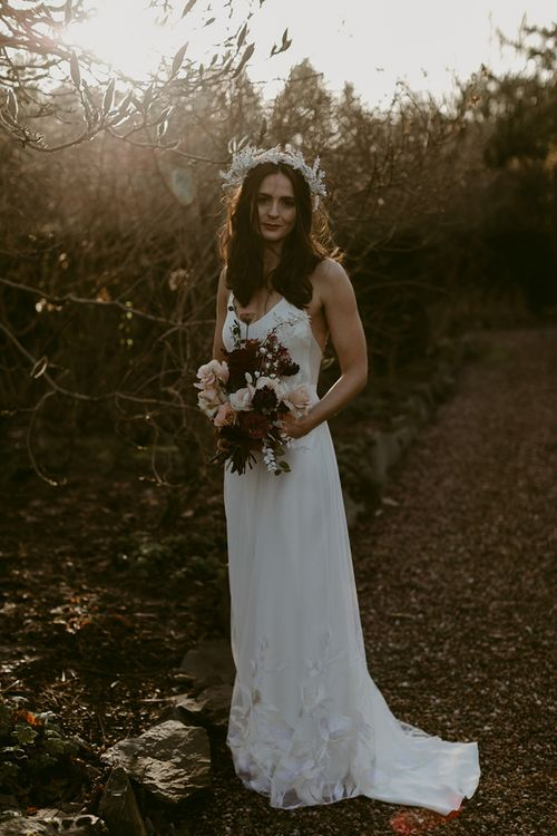 Stylish Bride in Halfpenny London Juniper Dress & Lilly Skirt and Luna Bea Headdress Holding Burgundy and Pink Wedding Bouquet