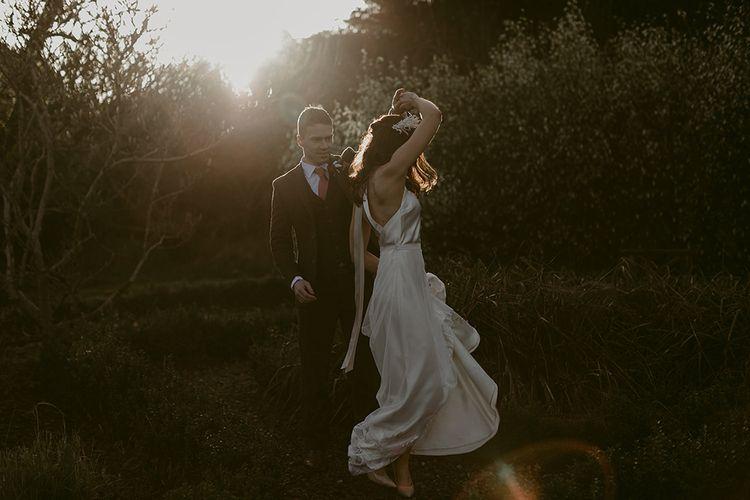 Groom in Brown Wool Suit Twirling his Bride in Halfpenny London Juniper Dress & Lilly Skirt and Luna Bea Headdress