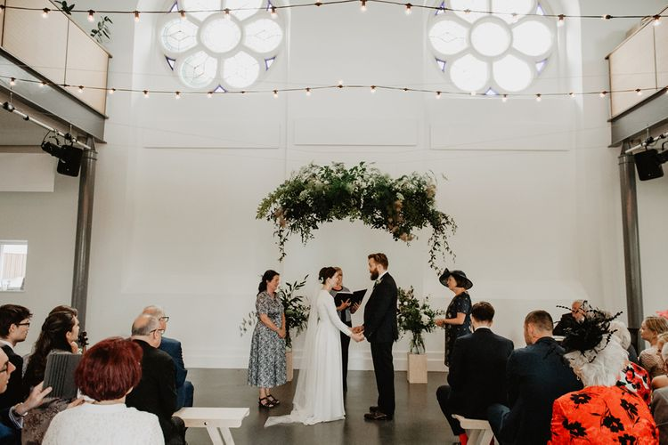 Wedding Ceremony with Hanging Greenery Installation and Fairy Light Wedding Decor